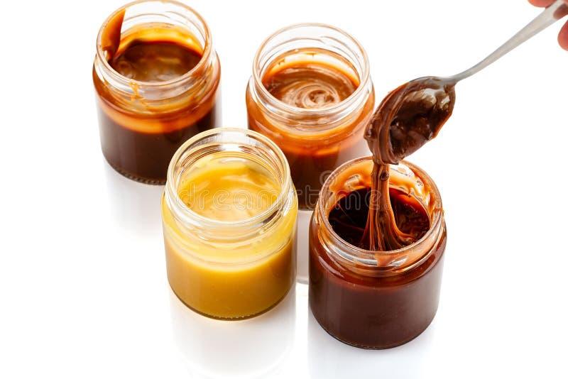 Metta delle salse casalinghe del caramello in barattoli isolati su fondo bianco fotografie stock
