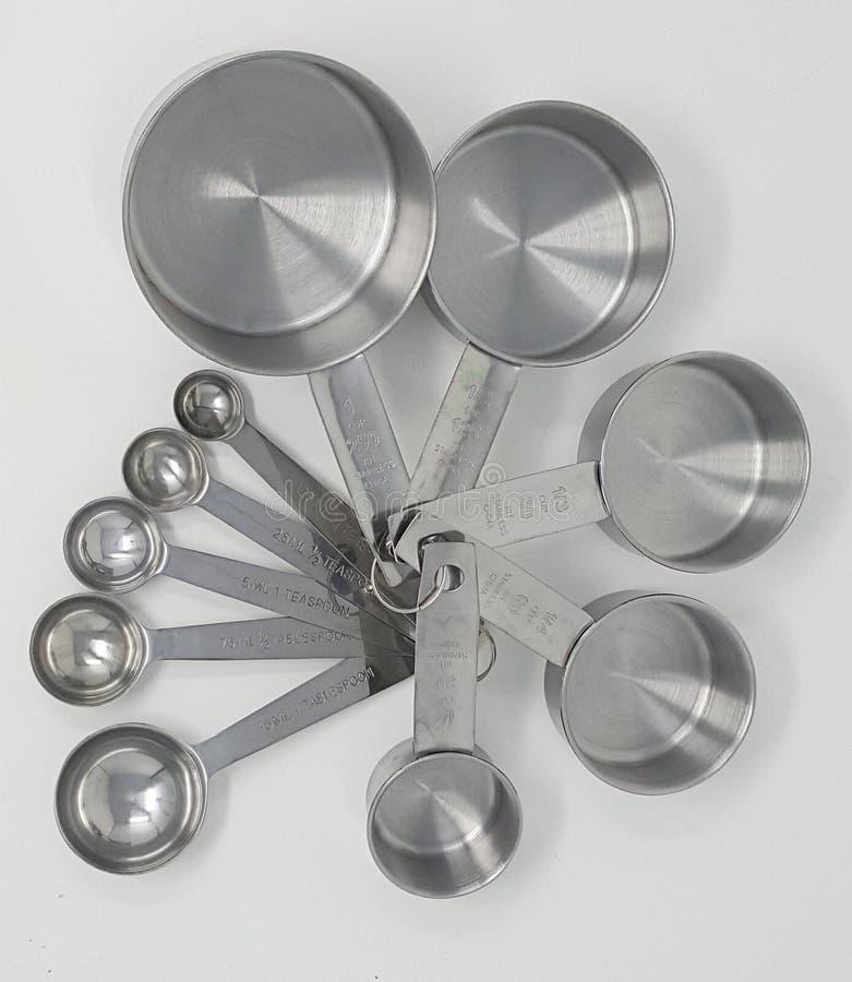 Metta delle tazze e dei cucchiai di misurazione di acciaio inossidabile fotografia stock libera da diritti
