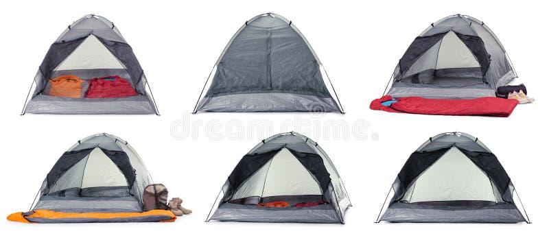 Metta delle tende comode e delle attrezzature di campeggio su bianco immagine stock