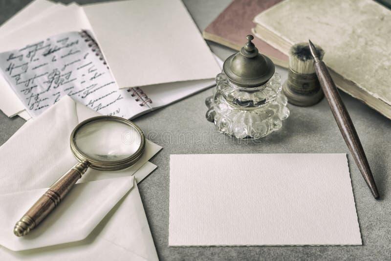 Metta di cancelleria d'annata, la penna di legno, il calamaio, lente e le buste, lettere si chiudono su Scrittura della lettera M fotografia stock libera da diritti