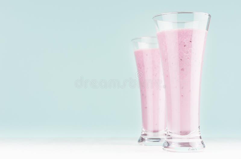 Metta di due bevande del latte di dieta con il mirtillo in vetro elegante su fondo blu-chiaro molle pastello, spazio della copia fotografia stock libera da diritti