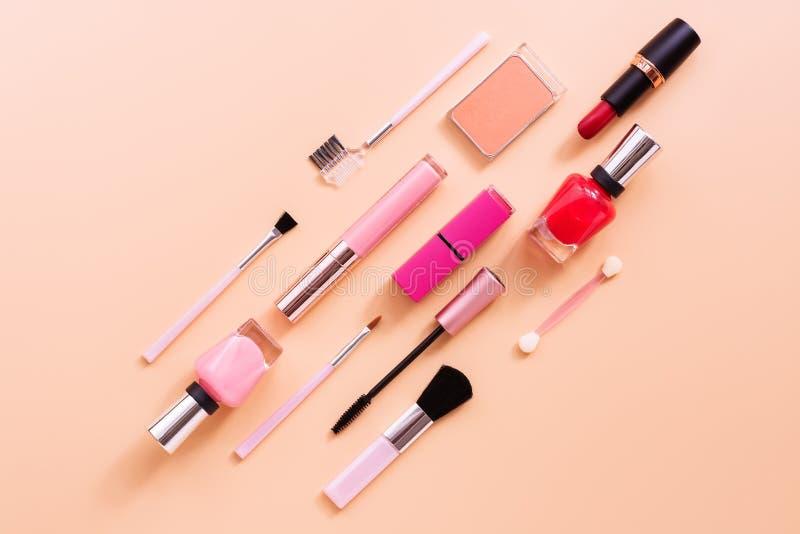 Metta di trucco femminile dei cosmetici su un fondo pastello rosa Disposizione piana, vista superiore, spazio della copia immagine stock libera da diritti