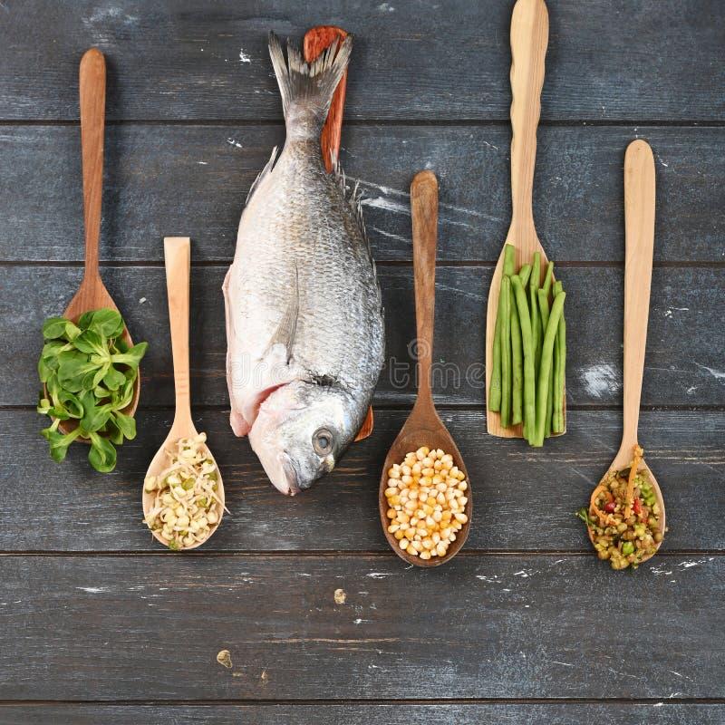 Metta di vari ingredienti in cucchiai di legno per alimento per animali domestici fotografia stock libera da diritti