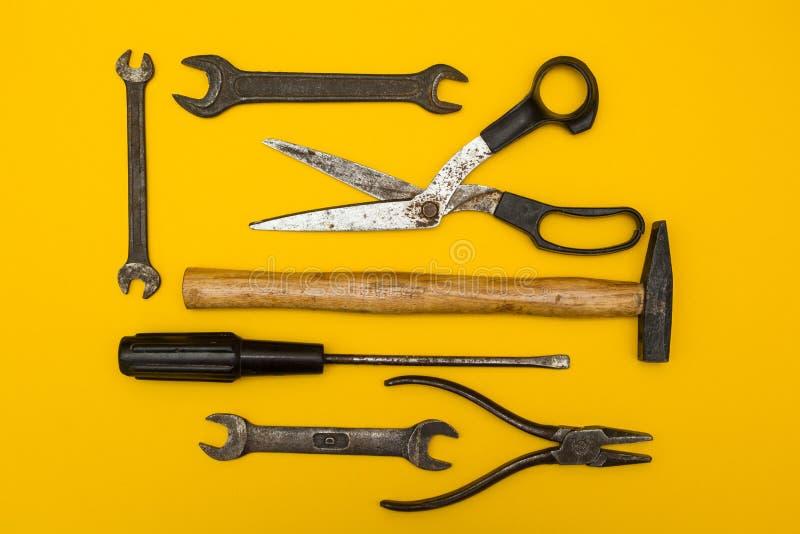 Metta di vecchi strumenti arrugginiti su un fondo giallo, con spazio per testo fotografia stock libera da diritti
