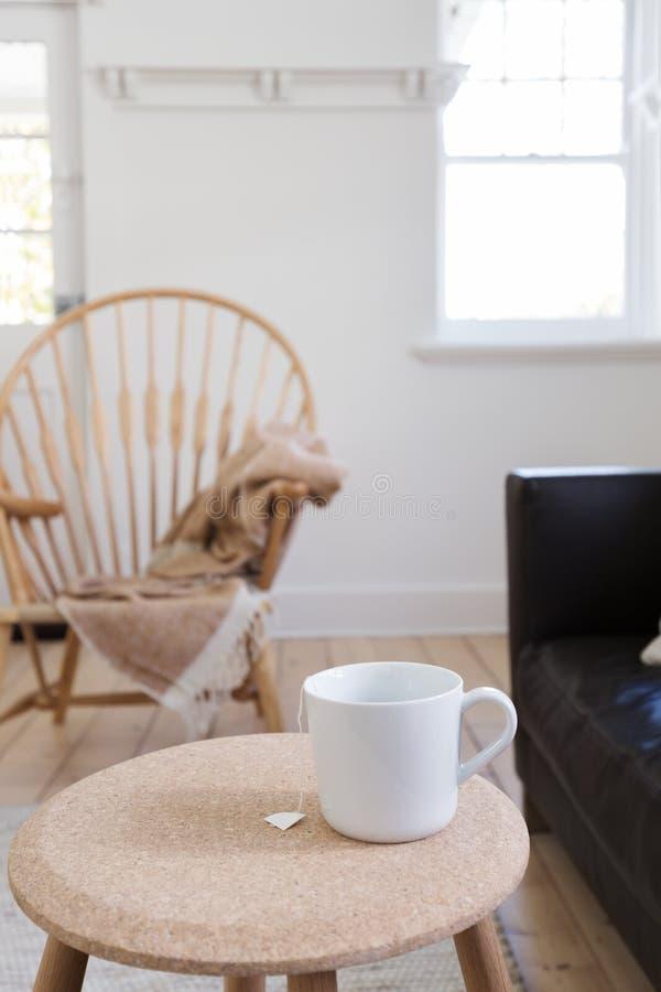 Metta a fuoco sulla tazza di tè in salone disegnato contemporaneo fotografie stock