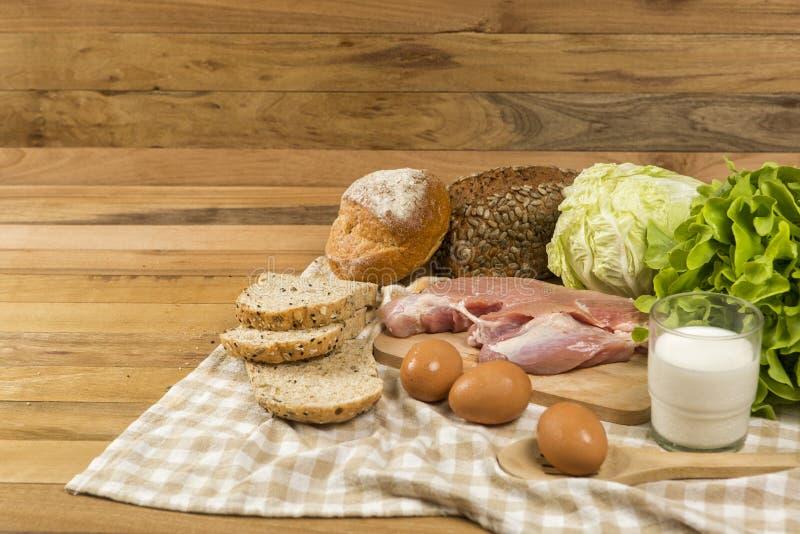 Metta i prodotti che consistono del pane, del latte, della carne di maiale, delle uova e della verdura sul fondo di legno della t fotografie stock libere da diritti