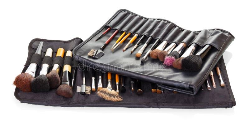 Metta le spazzole cosmetiche in coperture nere isolate su fondo bianco fotografie stock libere da diritti