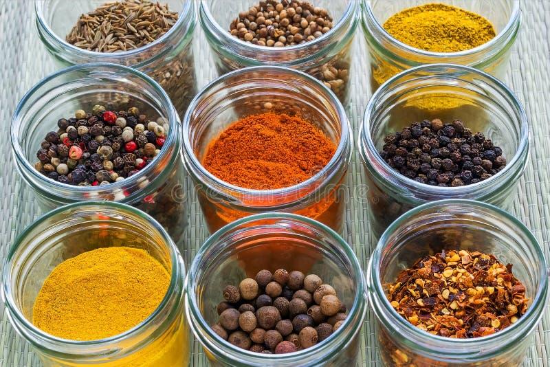 Metta le spezie del od nove ed i condimenti differenti dell'erba in barattoli di vetro su una stuoia verde ruvida Spezie e condim fotografie stock libere da diritti