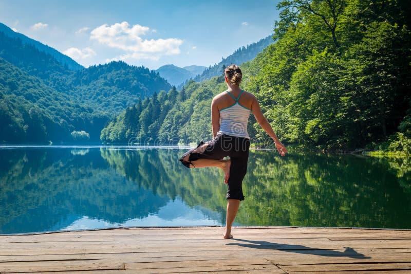 Metta in mostra gli esercizi ad aria fresca nel pilastro del lago della montagna immagini stock