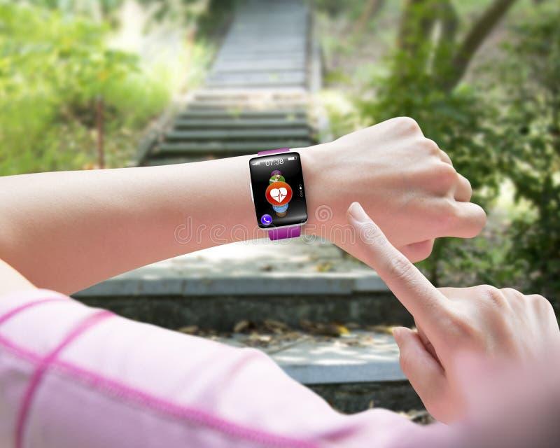 Metta in mostra il dito della donna che indica il weari astuto della mano dell'orologio del sensore di salute fotografia stock libera da diritti