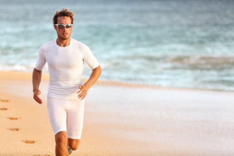 Metta in mostra l'addestramento dell'atleta sulla spiaggia per la corsa di triathlon fotografia stock libera da diritti
