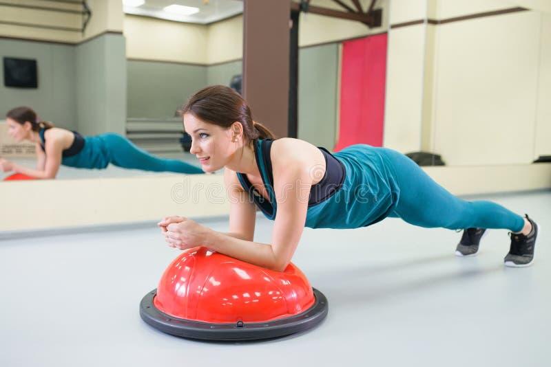 Metta in mostra l'esercizio con una palla dell'equilibrio alla palestra, posizione della donna della plancia immagine stock libera da diritti