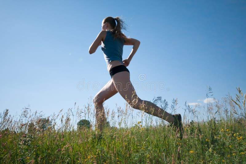 Metta in mostra la donna che funziona sopra l'erba verde ed il cielo fotografie stock
