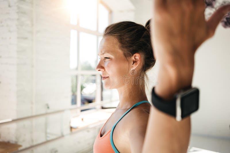 Metta in mostra la donna che indossa l'orologio astuto che fa l'allenamento di forma fisica fotografia stock libera da diritti