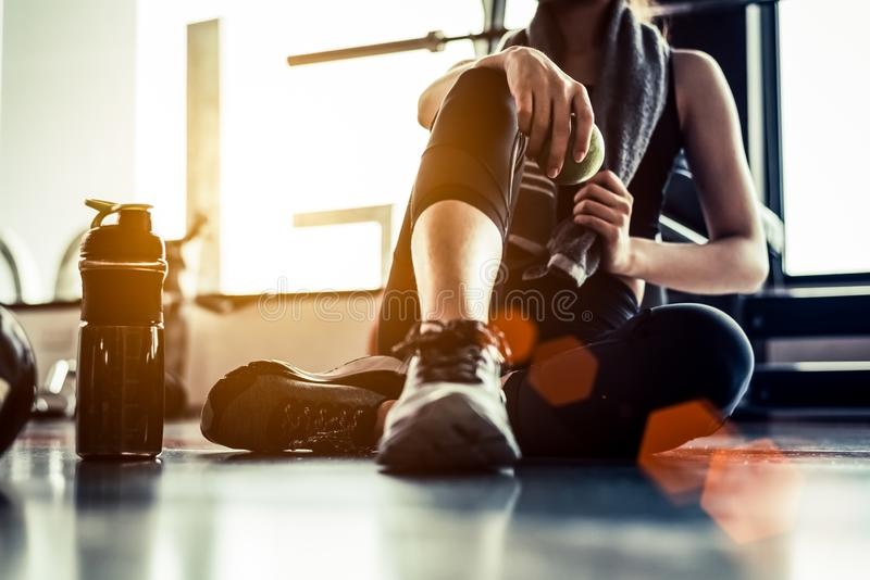 Metta in mostra la donna che si siede e che riposa dopo che allenamento o esercizio in palestra di forma fisica con la scossa del fotografia stock
