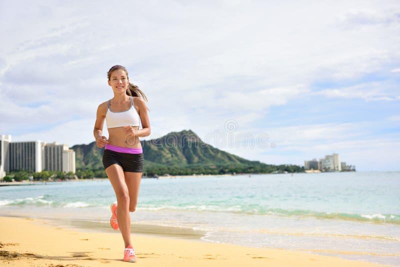 Metta in mostra la donna corrente di forma fisica che pareggia sul funzionamento della spiaggia immagini stock