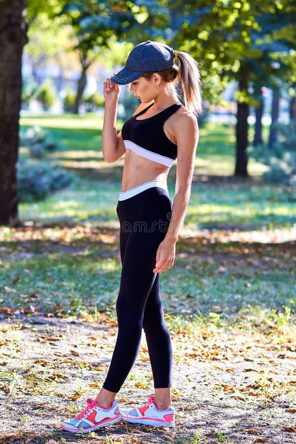 Metta in mostra la ragazza La ragazza sta facendo gli esercizi di forma fisica Il bello giovane mette in mostra la donna che fa g fotografia stock libera da diritti