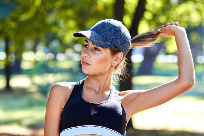 Metta in mostra la ragazza La ragazza sta facendo gli esercizi di forma fisica Il bello giovane mette in mostra la donna che fa g immagini stock