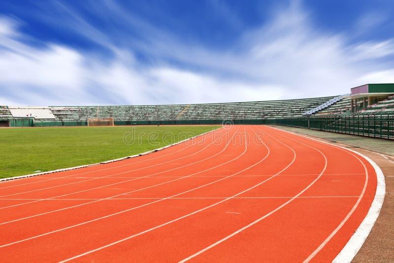Metta in mostra lo stadio con le linee correnti fondo della pista del cielo blu fotografie stock libere da diritti