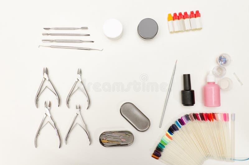 Metta per il manicure Strumenti, pinze, smalto, rivestimento, nappa e tavolozza Fondo bianco, vista superiore fotografia stock libera da diritti