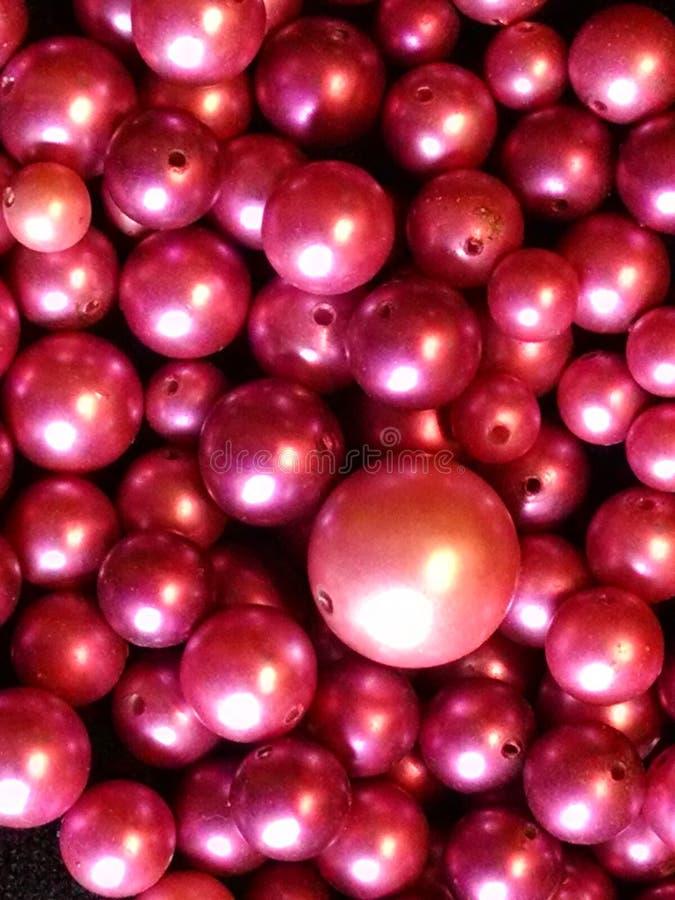 Metta in serbo delle perle pearlescent magenta impilate in un mucchio fotografie stock libere da diritti