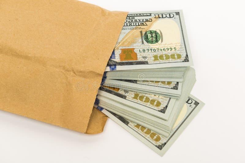 Metta in serbo di soldi in cento banconote del dollaro che escono dalla busta fotografia stock