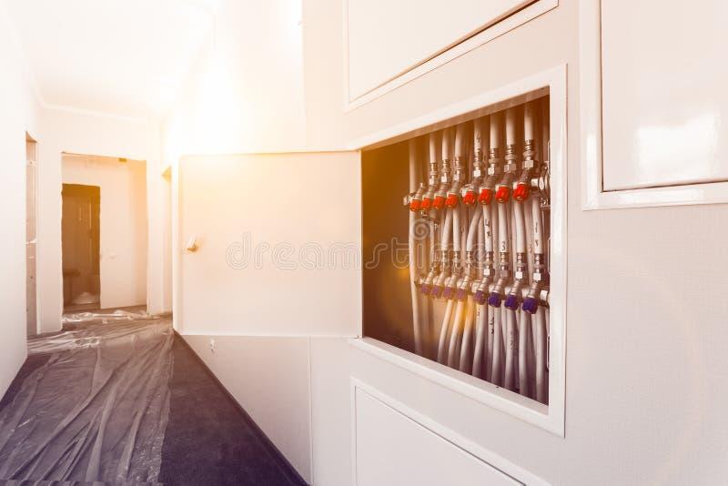 Mettant d'aplomb les tuyaux en plastique blancs, des garnitures et les robinets à tournant sphérique sont installés en appartemen photographie stock libre de droits
