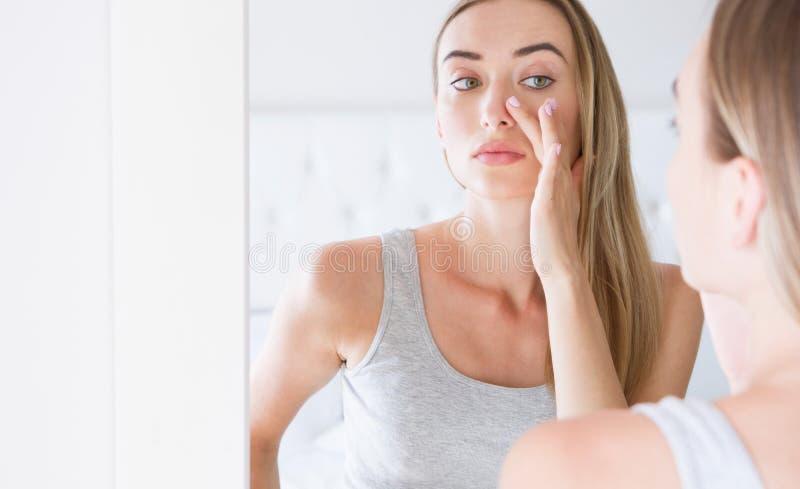 Mettant de la crème, beau regard de fille au miroir photos stock