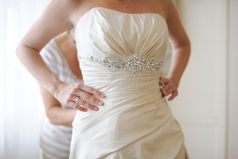 Mettant la robe de mariage en fonction image libre de droits