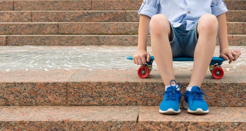 Mette in mostra il fondo, un ragazzo che si siede su un pattino sui punti fotografia stock libera da diritti