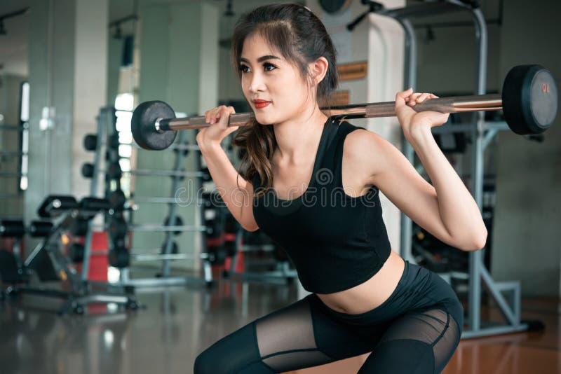 Mette in mostra il peso di sollevamento della donna nella palestra di forma fisica Esercizio di allenamento e concetto di accumul fotografie stock libere da diritti