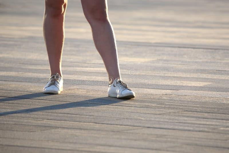 Mette in mostra le gambe del ` s della ragazza in scarpe da tennis fotografia stock libera da diritti