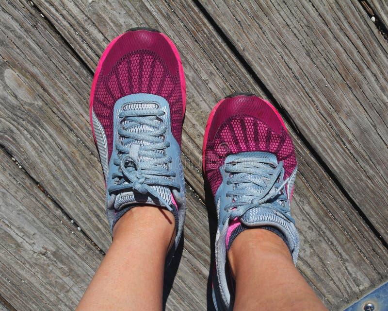 Mette in mostra le scarpe da corsa, con un bei sfondo naturale, parco e lago immagini stock