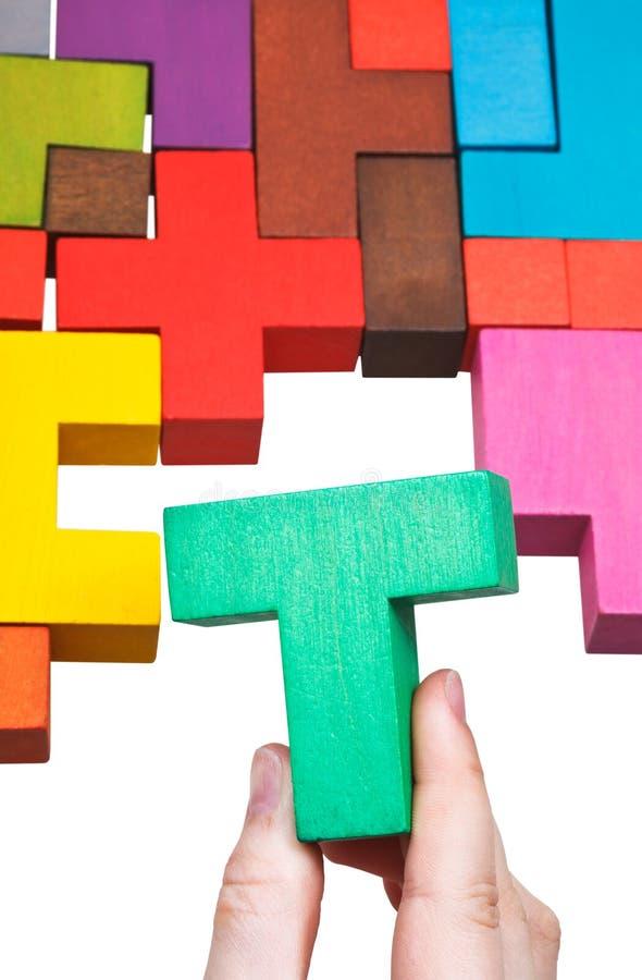 Mettendo blocco a forma di t nel puzzle multicoloured fotografia stock