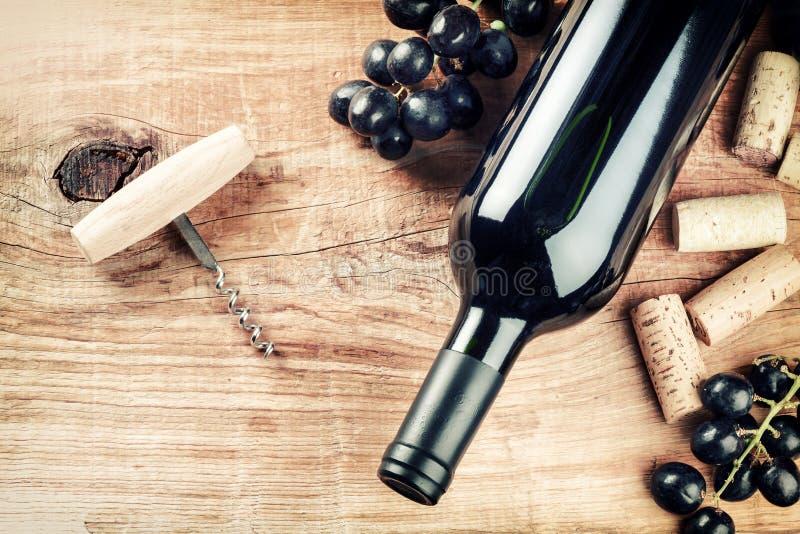 Mettendo con la bottiglia di vino rosso, dell'uva e dei sugheri Lista di vino concentrata fotografie stock