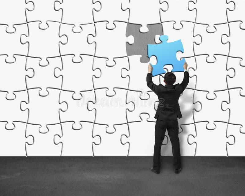 Mettendo puzzle blu unico nella parete fotografie stock libere da diritti