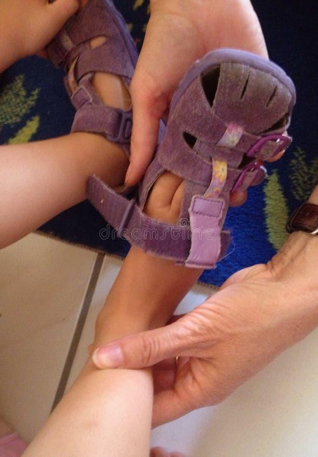 Mettendo sandalo su un piede del bambino fotografia stock