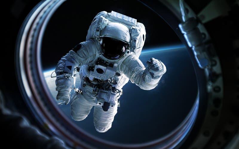 Mettez à la terre la planète et l'astronaute dans le hublot de fenêtre de vaisseau spatial Éléments de cette image meublés par la photo libre de droits