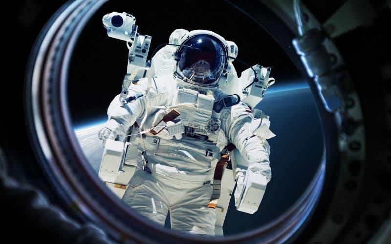 Mettez à la terre la planète et l'astronaute dans le hublot de fenêtre de vaisseau spatial Éléments de cette image meublés par la images stock