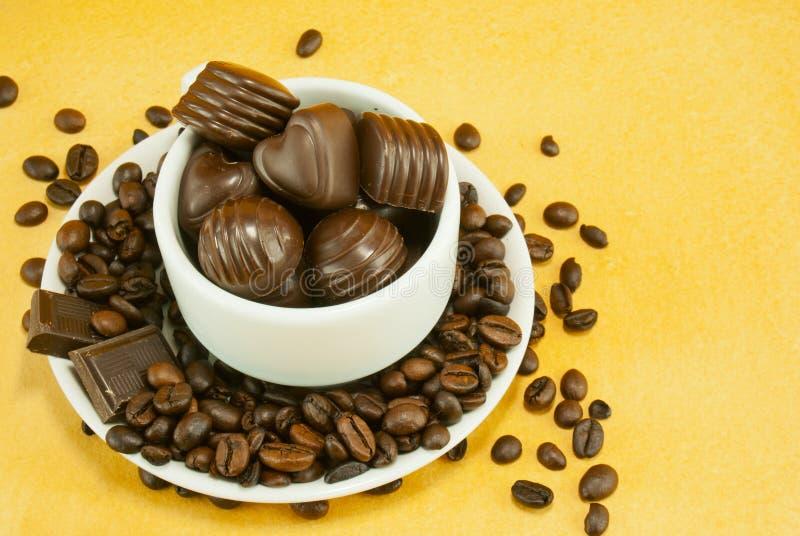 Mettez en forme de tasse complètement avec des grains de café et des sucreries de chocolat photographie stock libre de droits