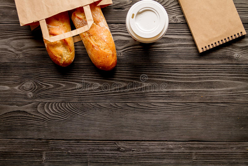 Mettez en forme de tasse le café et le pain dans le sac de papier sur le fond en bois photographie stock libre de droits