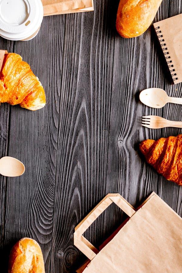 Mettez en forme de tasse le café et le pain dans le sac de papier sur le fond en bois photos libres de droits