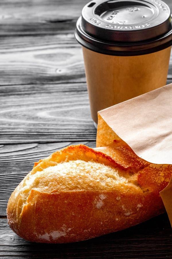 Mettez en forme de tasse le café et le pain dans le sac de papier sur le fond en bois photo libre de droits