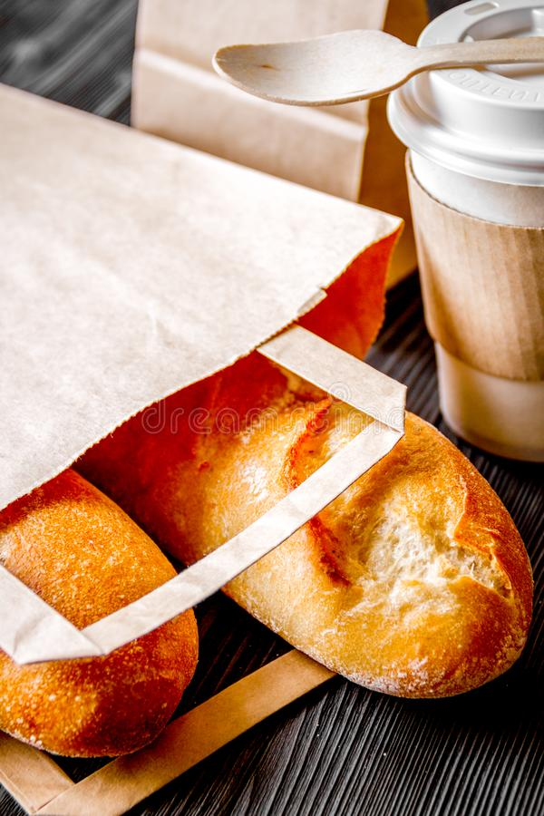 Mettez en forme de tasse le café et le pain dans le sac de papier sur le fond en bois images stock