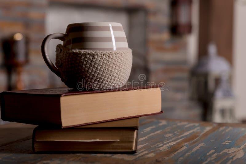 Mettez en forme de tasse le café ou thé chaud, cacao, écharpe et livres couverts par chocolat sur la table en bois, photo modifié photographie stock libre de droits