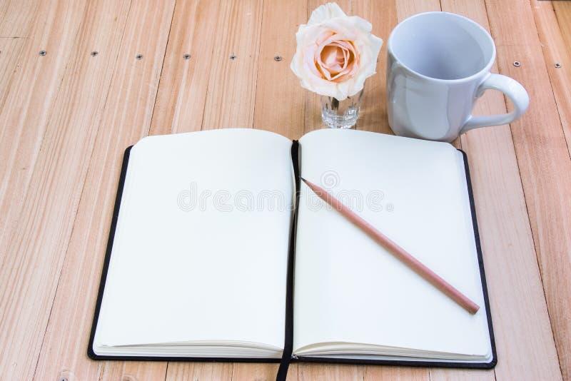 Mettez le crayon sur le carnet près de la tasse de café et vous êtes levé photographie stock libre de droits