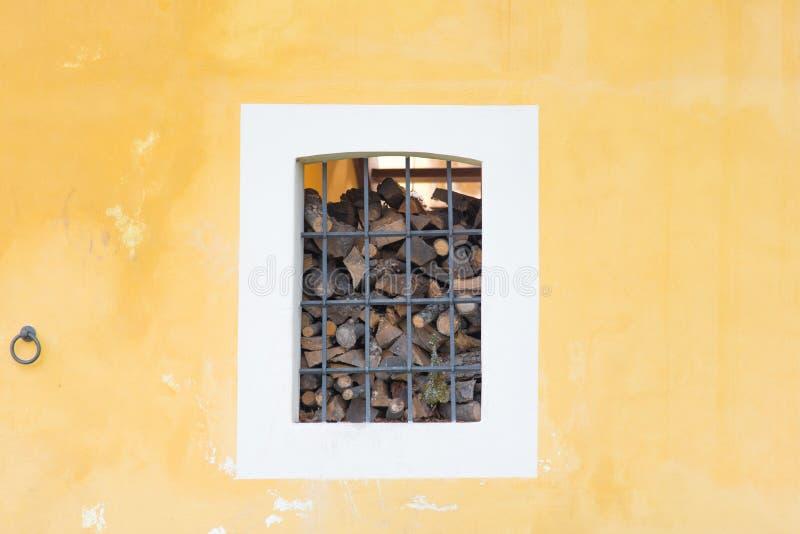 Mettez le feu au bois dans la cage carrée sur le mur rustique jaune photos stock