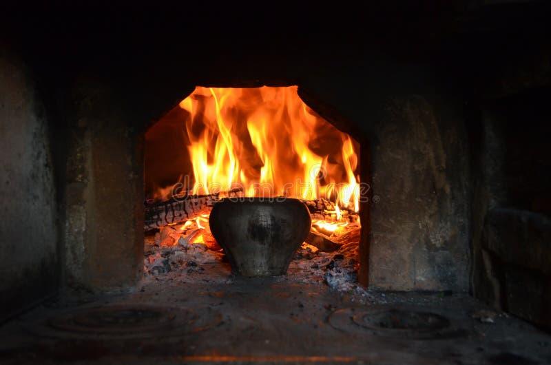 Mettez le feu au foyer du four russe et du vieux pot de fonte photographie stock