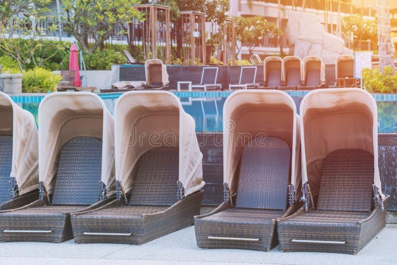 mettez le lit en commun près de la piscine dans la station de vacances tropicale image stock