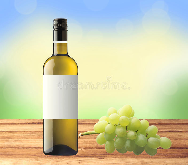 Mettez le vin blanc et le raisin en bouteille vert sur la table en bois au dessus de la nature - La bouteille sur la table ...